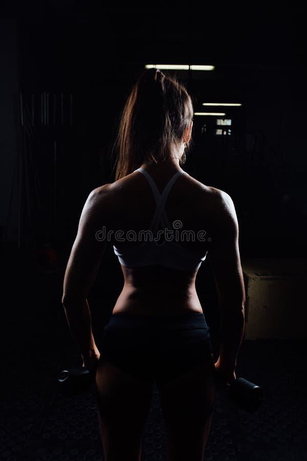 Bella donna di forma fisica con le teste di legno di sollevamento fotografie stock