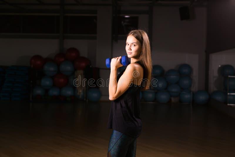 Bella donna di forma fisica con le teste di legno di sollevamento Donna sportiva che solleva i pesi leggeri Ragazza adatta che es fotografie stock libere da diritti