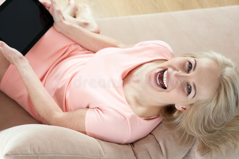 Bella donna di mezza età sorridente che si siede sullo strato con una compressa, tenendo conto di nuova idea immagini stock libere da diritti