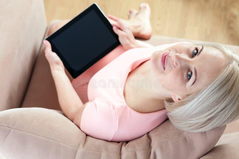 Bella donna di mezza età sorridente che si siede sullo strato con una compressa, tenendo conto di nuova idea fotografia stock