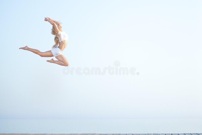 Bella donna di misura che salta alla spiaggia vicino immagini stock