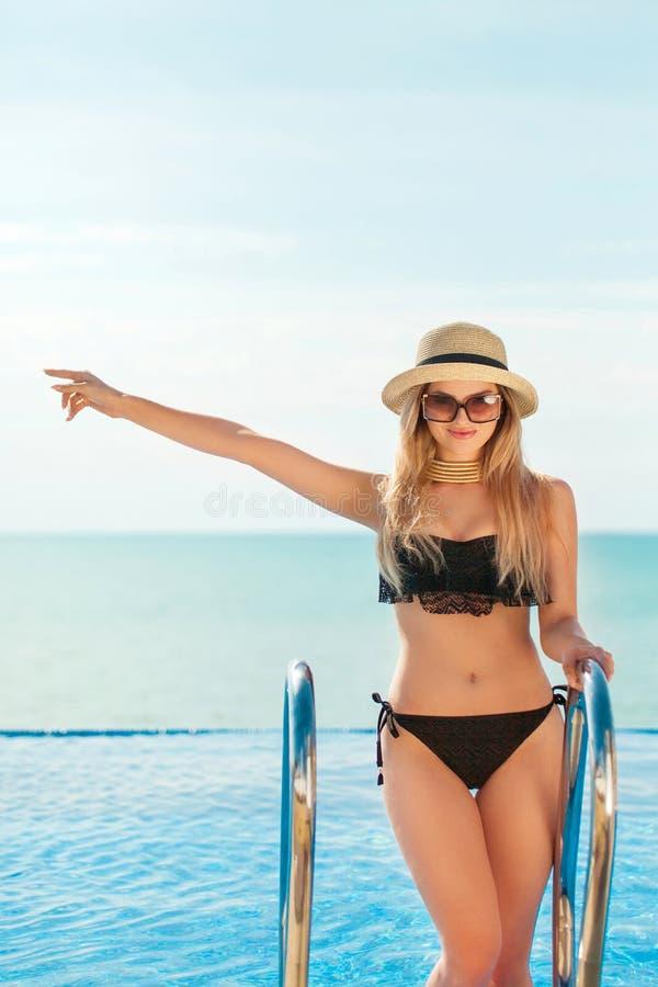 Bella donna di misura in vestito e cappello di nuotata nero che posano sulla spiaggia Vacanza di estate Indicare di modello sullo fotografia stock