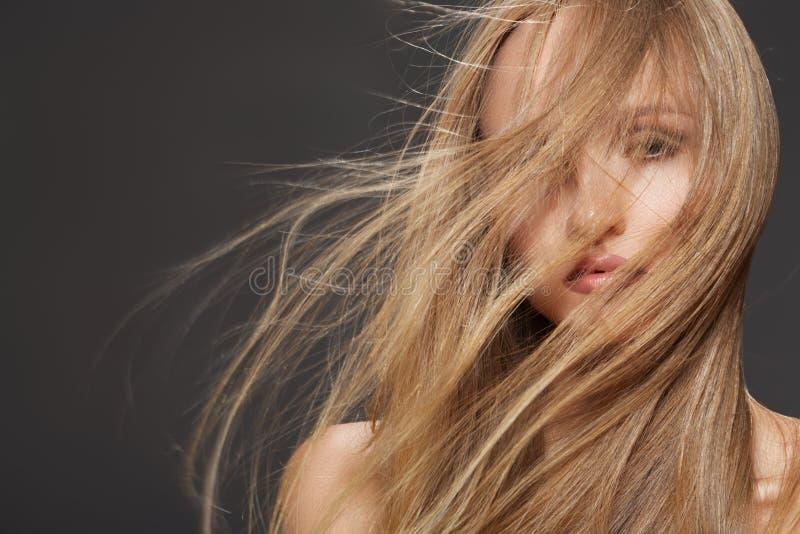Bella donna di modello che agita testa con capelli lunghi immagine stock