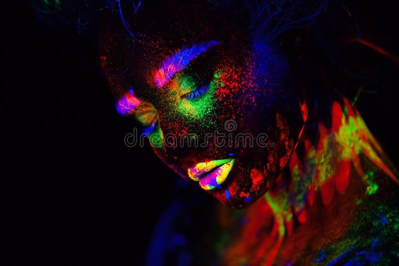 Bella donna di modello extraterrestra alla luce al neon È ritratto di bello modello con trucco fluorescente, arte fotografia stock libera da diritti