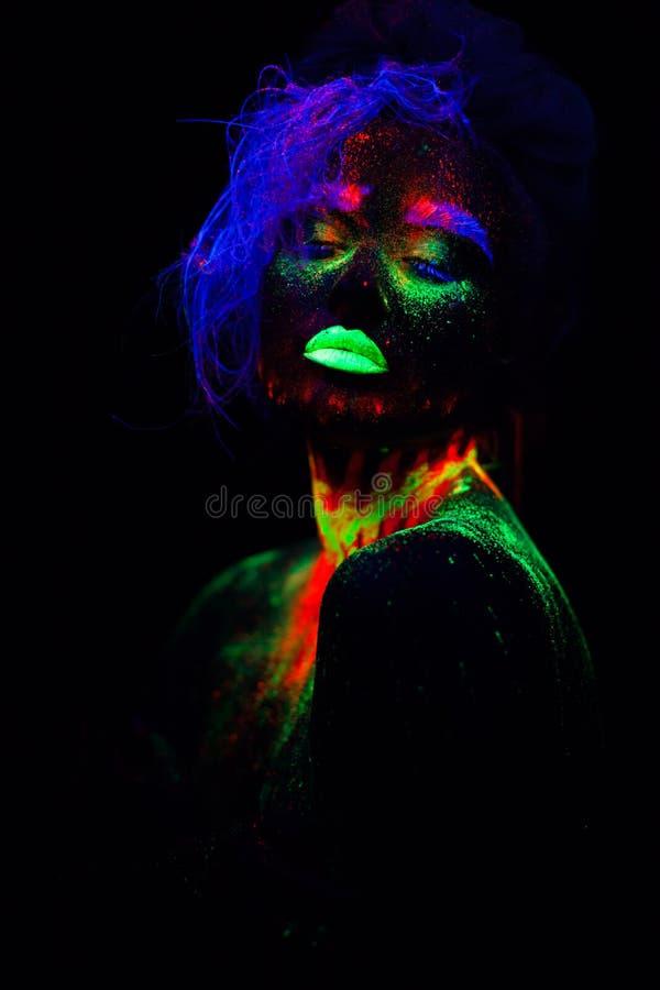 Bella donna di modello extraterrestra con capelli blu e le labbra verdi alla luce al neon È ritratto di bello modello fotografia stock