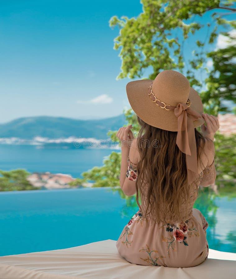 Bella donna di modo in cappello della spiaggia che gode della vista del mare dallo swimmi fotografia stock libera da diritti