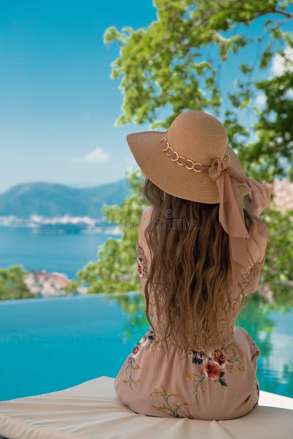 Bella donna di modo in cappello della spiaggia che gode della vista del mare dallo swimmi immagine stock libera da diritti