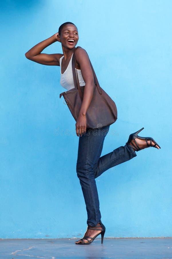 Bella donna di modo che sorride e che cammina con la borsa fotografia stock