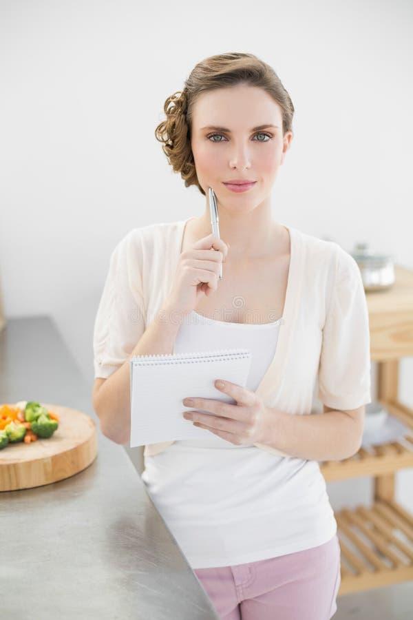 Bella donna di pensiero che redige una lista di acquisto che sta nella cucina immagini stock