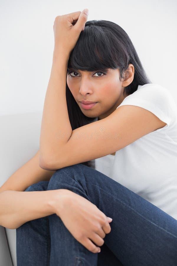 Bella donna di pensiero che si siede sullo strato in salone luminoso fotografia stock