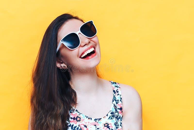 Bella donna di risata felice del yound in vestito ed occhiali da sole bianchi su fondo giallo fotografia stock libera da diritti