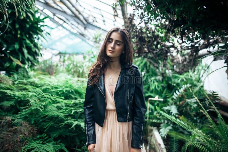 Bella donna di sogno con gli occhi chiusi che posano nel verde del giardino fotografia stock