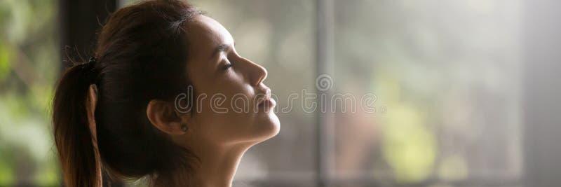 Bella donna di vista laterale con gli occhi chiusi che gode dell'aria fresca immagini stock