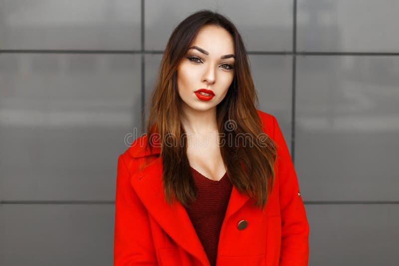Bella donna elegante con le labbra rosse in cappotto rosso alla parete immagine stock libera da diritti