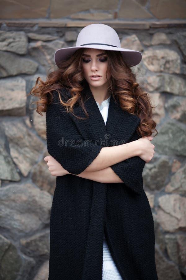 Bella donna elegante nel ove nero d'avanguardia alla moda del cappello e del cappotto fotografie stock libere da diritti