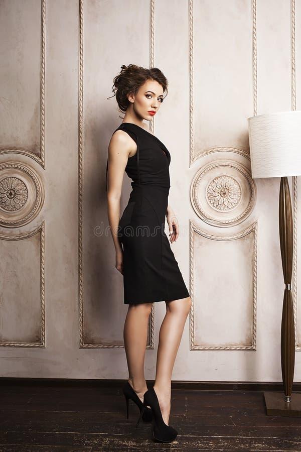 Bella donna elegante in vestito nero che sta vicino alla lampada di pavimento fotografia stock