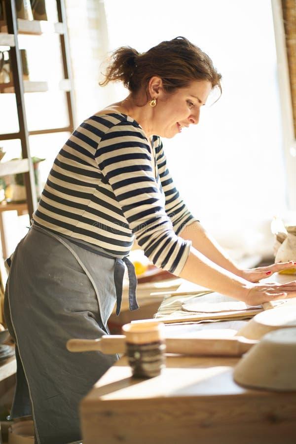 Bella donna felice che fa gli articoli ceramici in posto di lavoro, ridendo, sorridendo alla luce del sole Concetto per la donna  fotografia stock libera da diritti