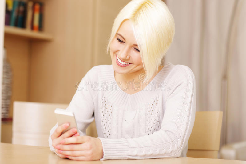 Bella donna felice che manda un sms sul suo smartphone fotografie stock libere da diritti