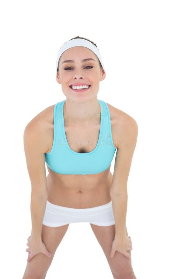 Bella donna felice che posa abiti sportivi d'uso che esaminano allegramente la macchina fotografica fotografie stock