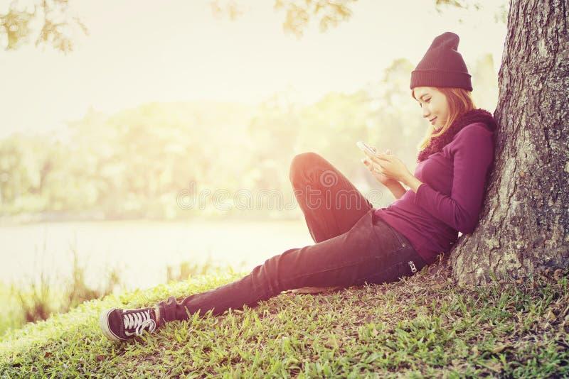 Bella donna felice che si siede sotto l'albero che gioca fon mobile fotografia stock libera da diritti