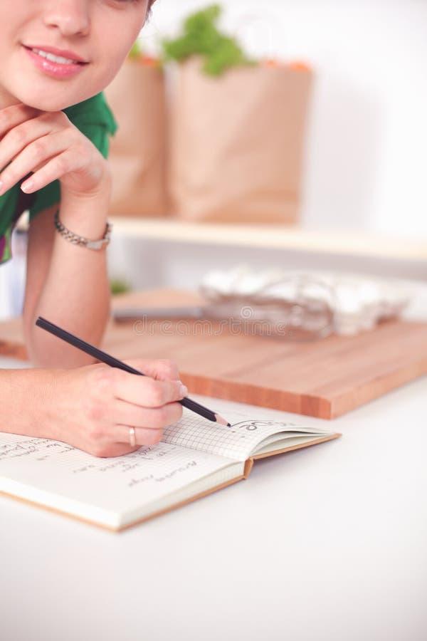 Bella donna felice che sta nella sua scrittura della cucina su un taccuino a casa fotografie stock libere da diritti