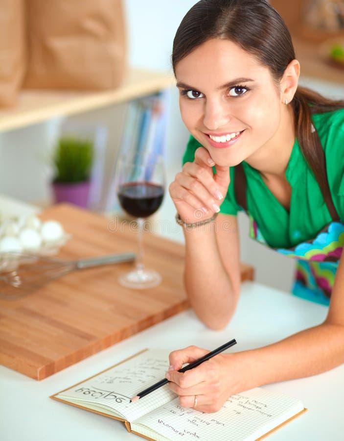 Bella donna felice che sta nella sua scrittura della cucina su un taccuino a casa immagine stock libera da diritti