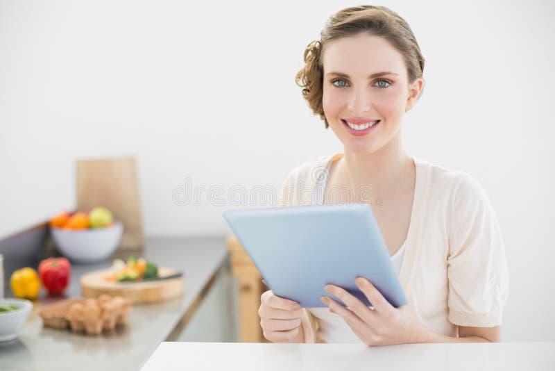 Bella donna felice che tiene la sua compressa che si siede nella sua cucina a casa fotografia stock libera da diritti