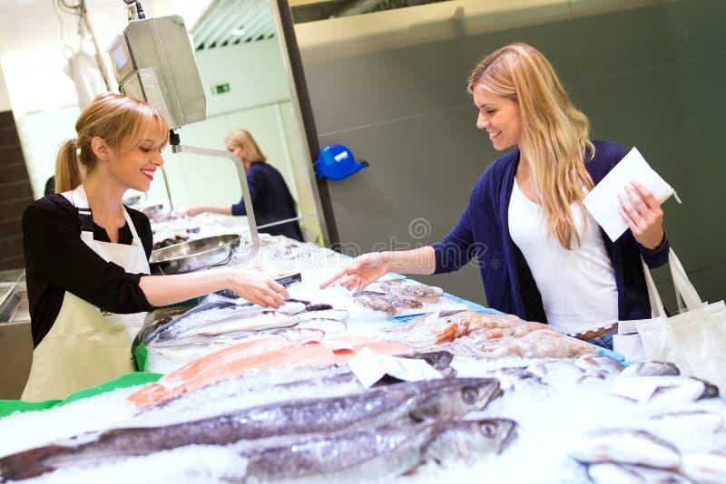 Bella donna felice che vende pesce fresco al cliente nel mercato fotografia stock libera da diritti