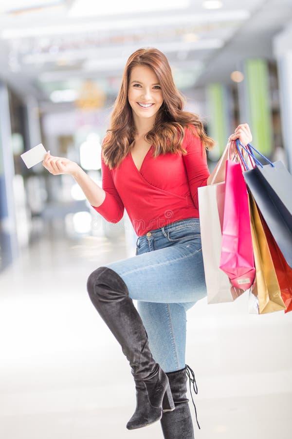 Bella donna felice con la carta di credito e sacchetti della spesa nel centro commerciale immagini stock libere da diritti