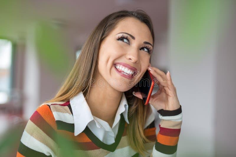 Bella donna felice di affari che parla sul telefono al offic immagine stock libera da diritti