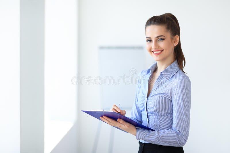 Bella donna felice di affari con la lavagna per appunti nell'ufficio fotografia stock
