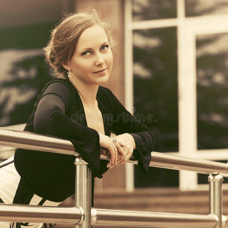 Bella donna felice di modo in blusa nera che si appoggia inferriata immagini stock