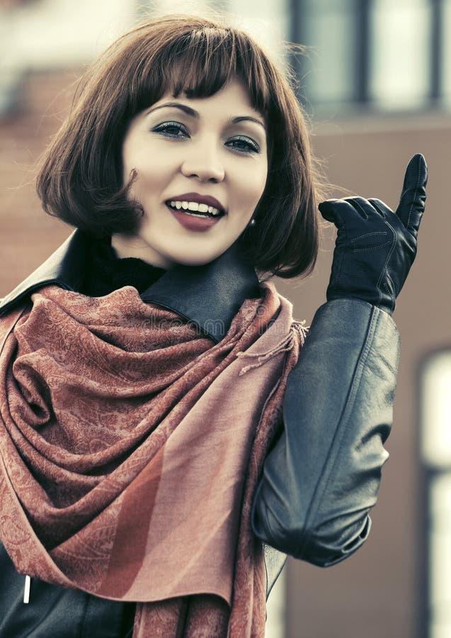 Bella donna felice di modo in cappotto di cuoio che cammina in via della città fotografie stock libere da diritti