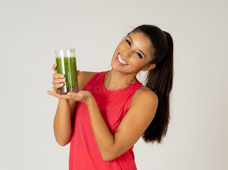 Bella donna felice di sport di misura che sorride e che beve il frullato sano della verdura fresca fotografie stock libere da diritti