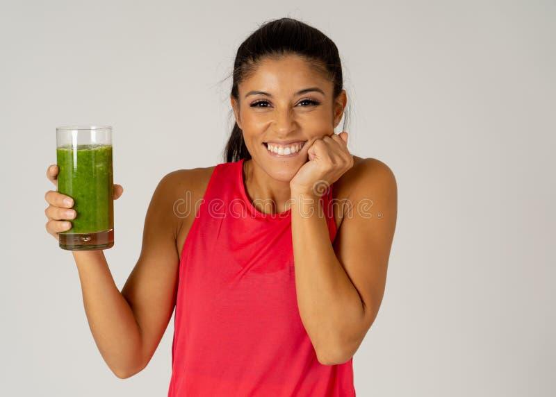 Bella donna felice di sport di misura che sorride e che beve il frullato sano della verdura fresca fotografie stock