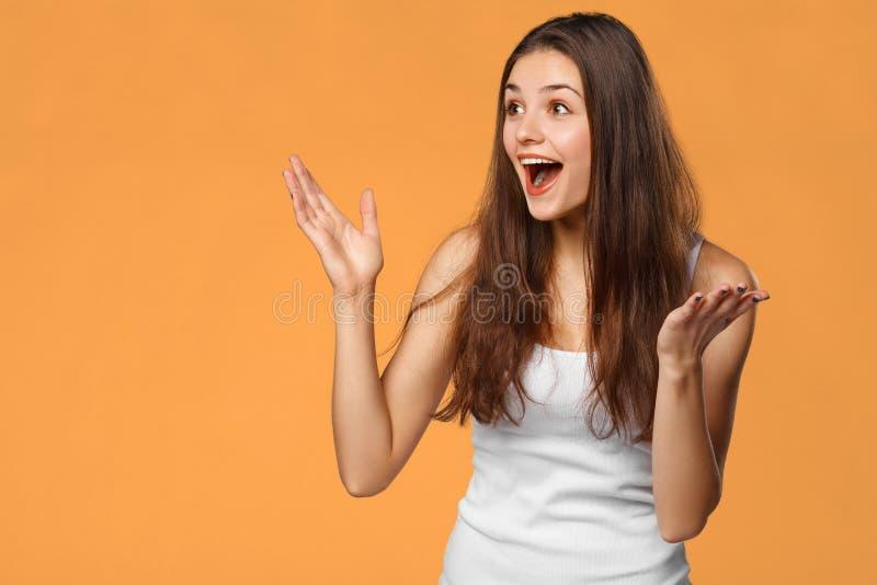 Bella donna felice sorpresa che guarda lateralmente nell'eccitazione, isolata su fondo arancio fotografie stock libere da diritti