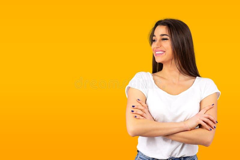 Bella donna felice sveglia che posa sul giallo fotografie stock