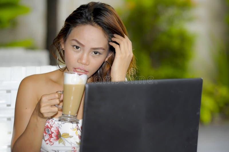 Bella donna felice in vestito da estate all'aperto alla caffetteria piacevole che ha rete della prima colazione o che lavora con  fotografia stock