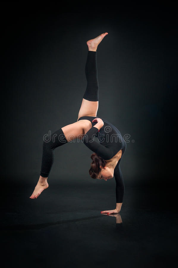 Bella donna flessibile che fa gli elementi acrobatici contro la b scura fotografia stock