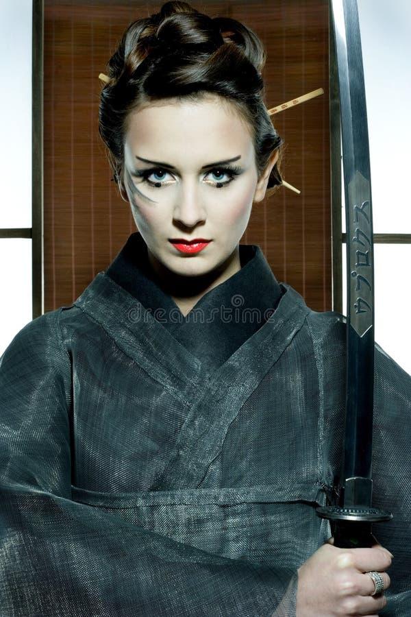 Bella donna giapponese del kimono con la spada del samurai fotografia stock