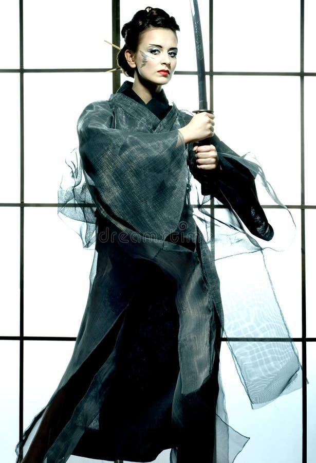 Bella donna giapponese del kimono con la spada del samurai fotografie stock