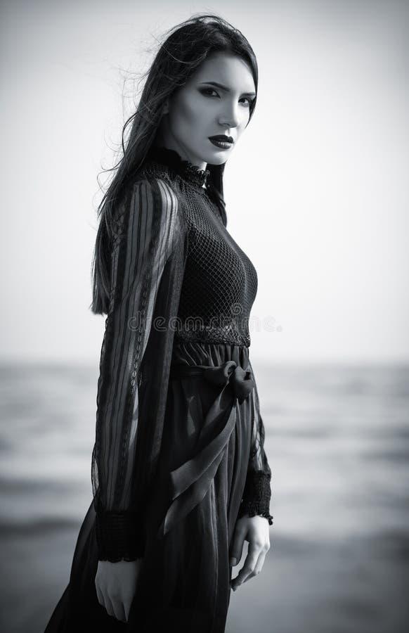 Bella donna gotica triste in vestito nero che sta sulla spiaggia del mare Rebecca 36 fotografia stock libera da diritti