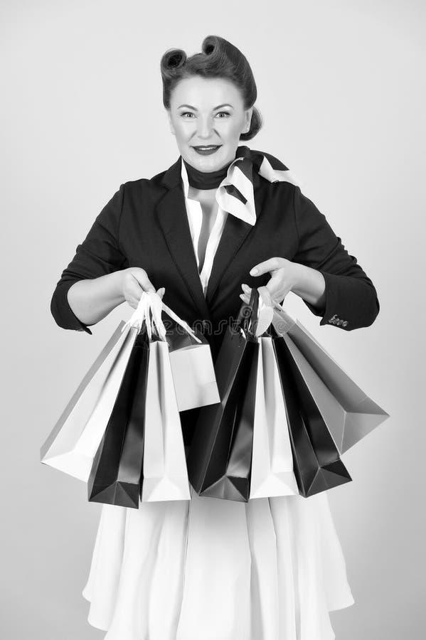 Bella donna graziosa in rivestimento con i sacchi di carta di compera colorati fotografia stock libera da diritti