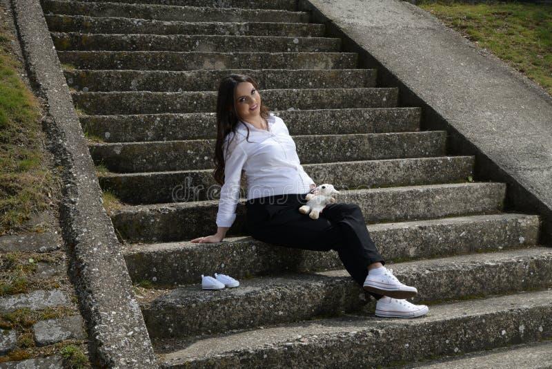 Bella donna incinta castana che si siede sulle scala di pietra nel parco della città fotografia stock libera da diritti