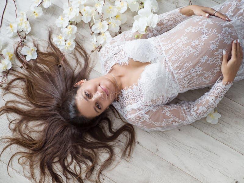 Bella donna incinta che abbraccia pancia che si trova sulla parte posteriore fra i fiori bianchi immagini stock libere da diritti