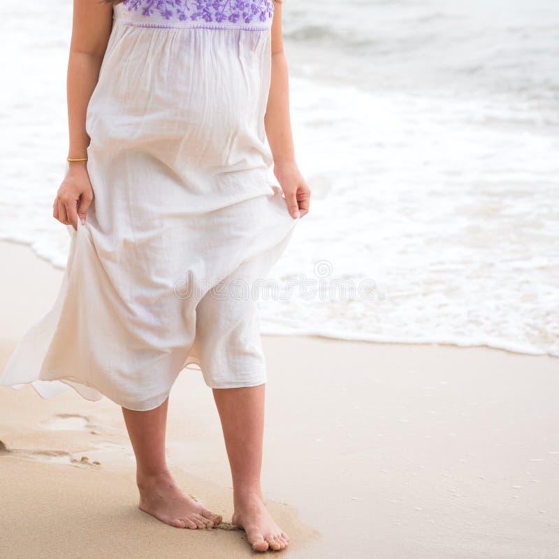 Bella donna incinta che cammina sul contatto tropicale della mano della spiaggia fotografie stock