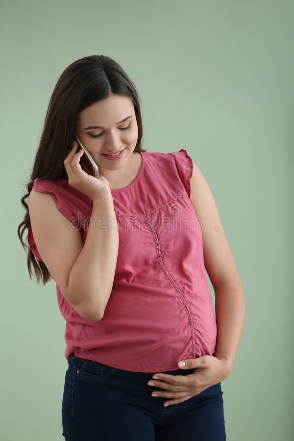 Bella donna incinta che parla dal telefono cellulare sul fondo di colore immagini stock