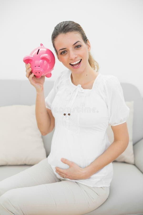 Bella donna incinta che scuote un porcellino salvadanaio mentre tenendo la sua pancia immagine stock
