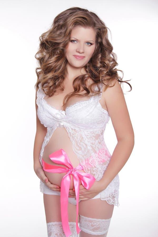 Bella donna incinta che segna la sua pancia del regalo isolata sul whi fotografia stock libera da diritti