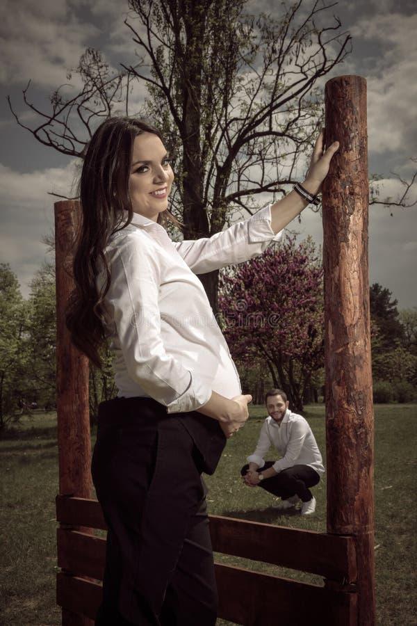 Bella donna incinta che si appoggia recinto di legno fotografie stock